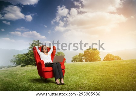 relaxed woman with closed eyes sitting on the red chair with laptop on green meadow over hill and blue sky - stock photo