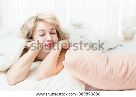 Relaxed young attractive blond girl lying on the bed closed eyes. Good night. Sweet Dreams