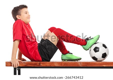 Relaxed young boy in football uniform sitting on a wooden bench and thinking isolated on white - stock photo
