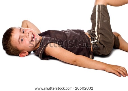 Relaxed young boy lying on his back smiling, isolated on a white background - stock photo