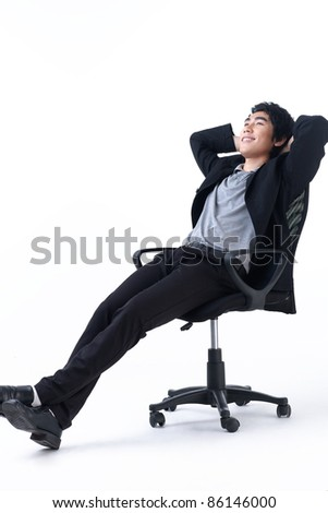 Relaxed young business man sitting on the chair - stock photo