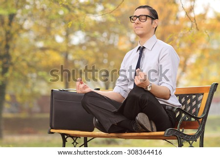 Relaxed young businessman meditating seated on a bench in park - stock photo