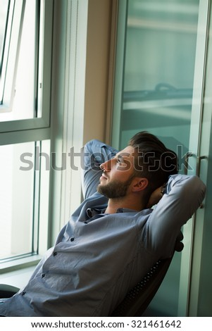 Relaxed young businessman reclining in his office - stock photo