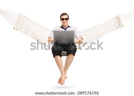 Relaxed young businessman sitting on a hammock and working on laptop isolated on white background - stock photo