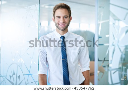 Relaxed young businessman with a charming smile, leaning casually against a patterned office divider in a modern workplace - stock photo