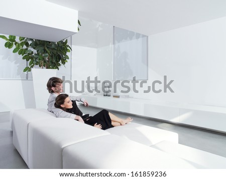 Relaxed young couple at home in bright living room - stock photo