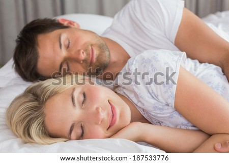 Relaxed young couple lying in bed with eyes closed at home - stock photo