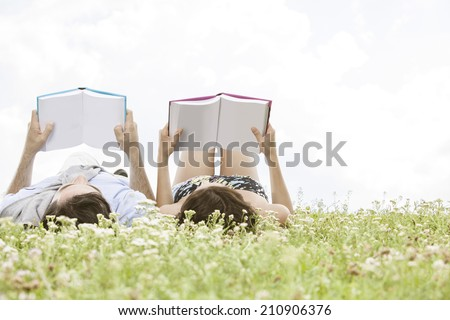Relaxed young couple reading books while lying on grass against sky - stock photo
