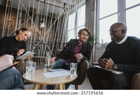 Relaxed young executives having a meeting indoors. Multiracial group of people sitting in office lobby discussing business. - stock photo