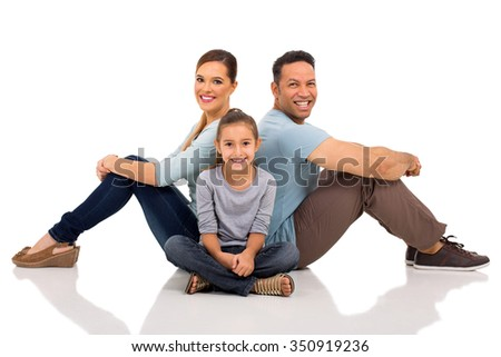 relaxed young family sitting on the floor - stock photo
