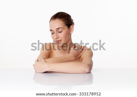relaxed young female model meditating with eyes closed massaging her neck,leaning on white glass for bodycare treatment,studio shot,white background - stock photo