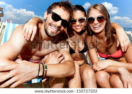 Relaxed young friends having rest on the beach - stock photo