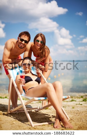 Relaxed young friends having rest on the beach on a sunny day - stock photo