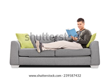 Relaxed young guy reading a book on a sofa isolated on white background