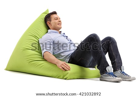 Relaxed young guy sitting on a soft and comfortable green beanbag isolated on white background - stock photo