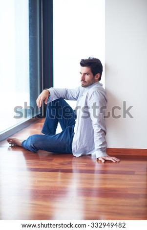 relaxed young man drink first morning coffee at modern home indoors at rainy window drops window