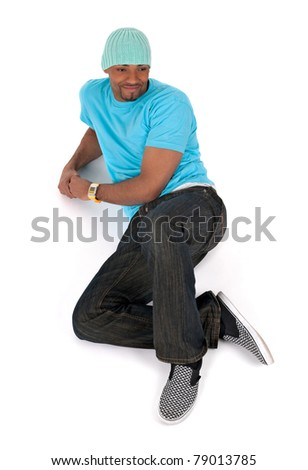 Relaxed young man in a blue t-shirt lying down smiling. Isolated on white background.