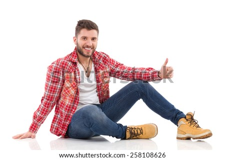 Relaxed young man in lumberjack shirt sitting on a floor and showing thumb up. Full length studio shot isolated on white. - stock photo