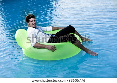 Relaxed young man on pool - stock photo