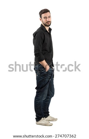 Relaxed young man side view looking at camera. Full body length portrait isolated over white background. - stock photo