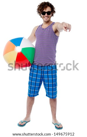 Relaxed young man with beach ball enjoying vacation - stock photo