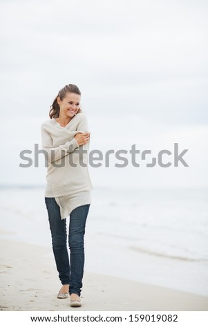 Relaxed young woman in sweater walking on lonely beach - stock photo