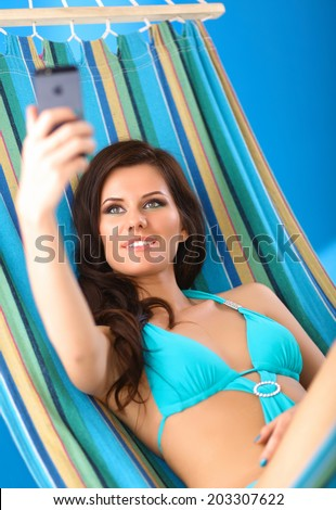 Relaxed young woman looking at mobile phone in hammock - stock photo