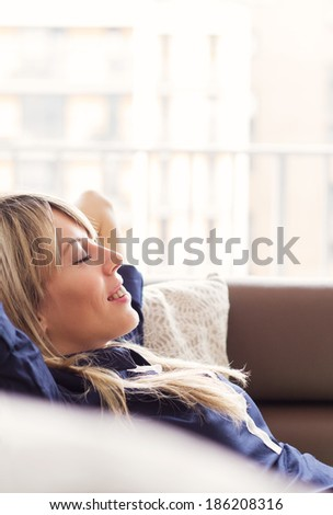 Relaxed young woman lying on couch - stock photo