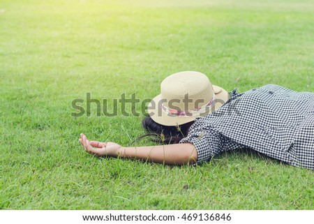 Relaxed young woman lying on the green grass - closed eyes