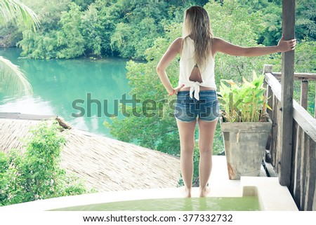 Relaxed young woman on the edge of swimming pool looking at beautiful view - stock photo