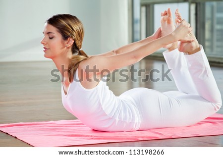 Relaxed young woman practicing yoga exercise called Bow Pose