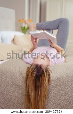 Relaxed young woman reading at home as she lies barefoot on her back on the bed with her long hair dangling over the edge