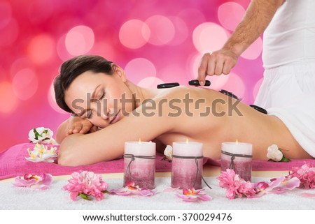 Relaxed young woman receiving hot stone therapy in beauty spa - stock photo