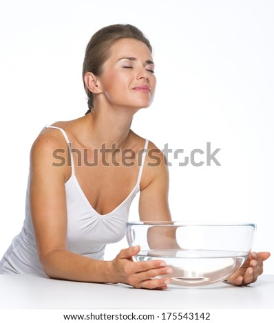 Relaxed young woman with glass bowl with water