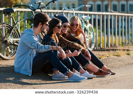 Relaxing after day riding. Group of young smiling people bonding to each other and looking at smart phone while sitting outdoors together with bicycles in the background  - stock photo