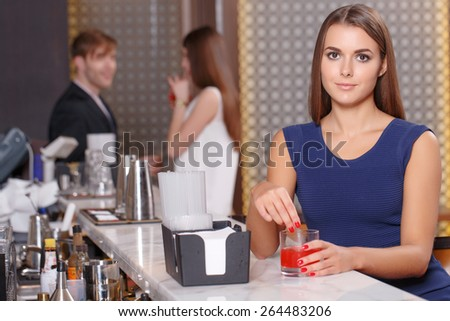 Relaxing after the job. Front shot of a beautiful woman holding a glass at the bar counter with young couple talking on the background - stock photo