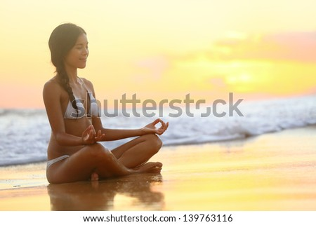 Relaxing and meditation - Yoga woman meditating at serene beach sunset. Girl relaxing in lotus pose in calm zen moment in the ocean water during yoga holidays resort retreat. Multiracial girl. - stock photo