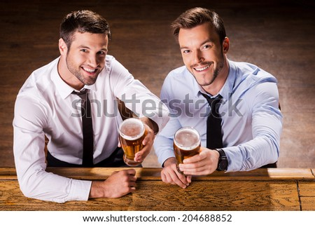 Relaxing at Friday night. Top view of two cheerful young men in shirt and tie holding glasses with beer and smiling while sitting at the bar counter  - stock photo