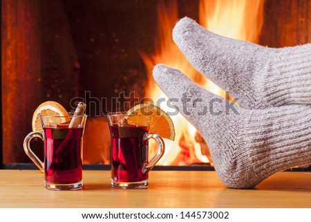 relaxing at the fireplace on winter evening with tea or mulled wine - stock photo