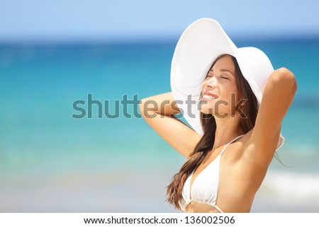 Relaxing beach woman enjoying the summer sun happy standing in a wide sun hat at the beach with face raised to the sunlight. Head and shoulder portrait. Multicultural Asian Caucasian in enjoyment. - stock photo