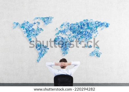 Relaxing businessman in front of world map made of social networking icons.  - stock photo