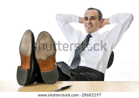 Relaxing businessman with feet up on his desk - stock photo