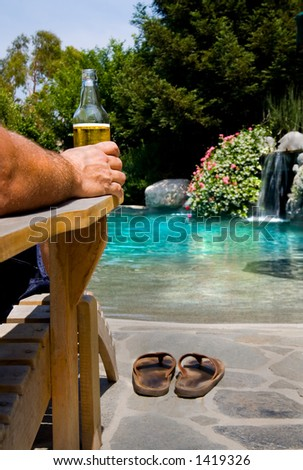 Relaxing by the pool on a hot summer day. - stock photo