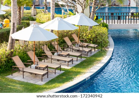 Relaxing chairs beside of swimming pool in residential garden - stock photo