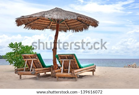 Relaxing couch chairs with bamboo parasol on white sandy Beach looking towards ocean and blue sky - stock photo