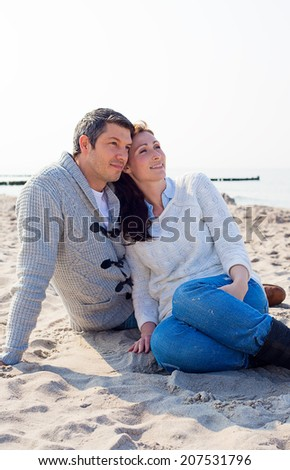 relaxing couple looking the wide sea and the sun going down - stock photo