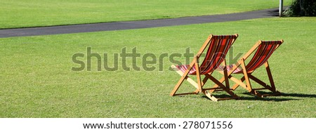 Relaxing garden chairs in garden setting surrounded by grass - stock photo