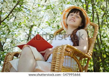 Relaxing  girl  in rocking-chair against blossoming garden