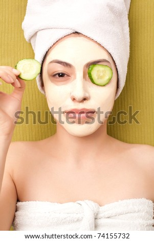 Relaxing girl with clay on her face - stock photo