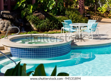 Relaxing hot tub by side of swimming pool with blue table and chairs - stock photo